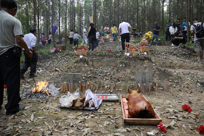 Clan members make offerings of meat and incense at their ancestral graves