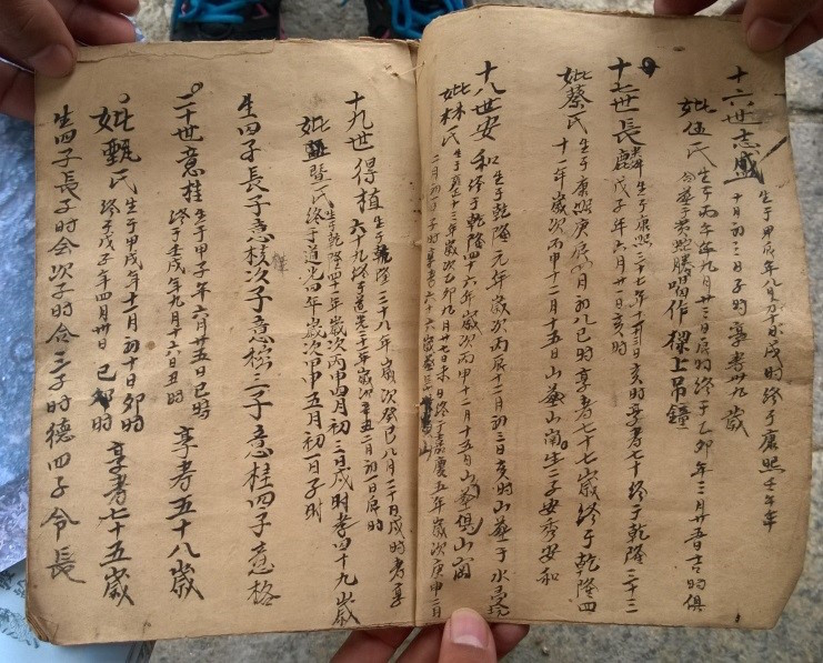 Hands holding an ancient zupu written in Chinese calligraphy