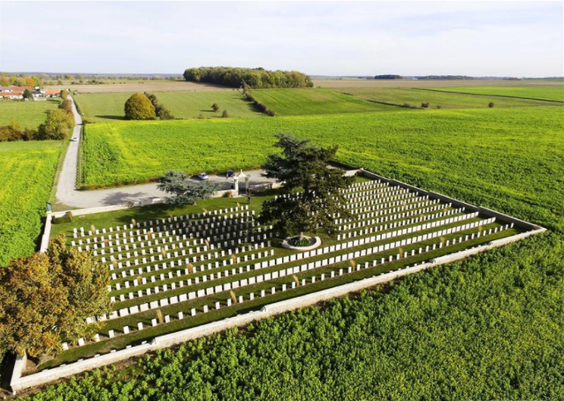 Large green field open space with many Chinese tombstones in Noyelles-sur-Mer cemetery