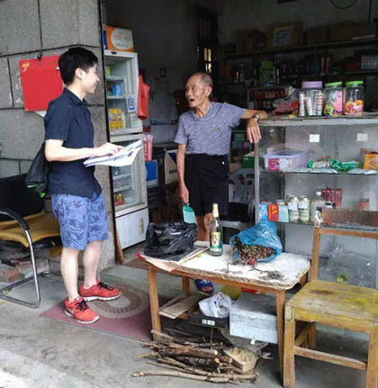MCR researcher Waikwan speaks with a villager at a storefront