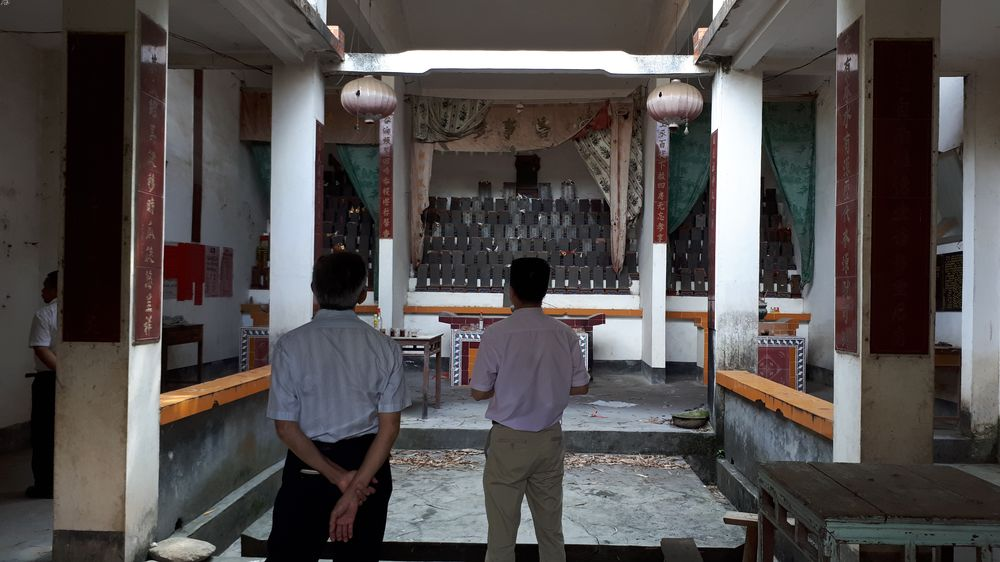 Two men standing in a dimly lit ancestral hall, their backs to the camera, with the ancestral tablets in the background.