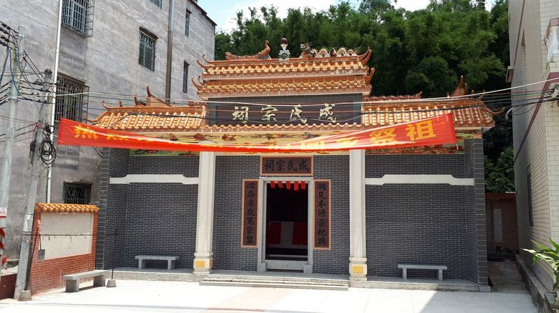 A newly completed 成Chinese ancestral hall with a dark grey brick façade, orange roof tiles, and a red banner.