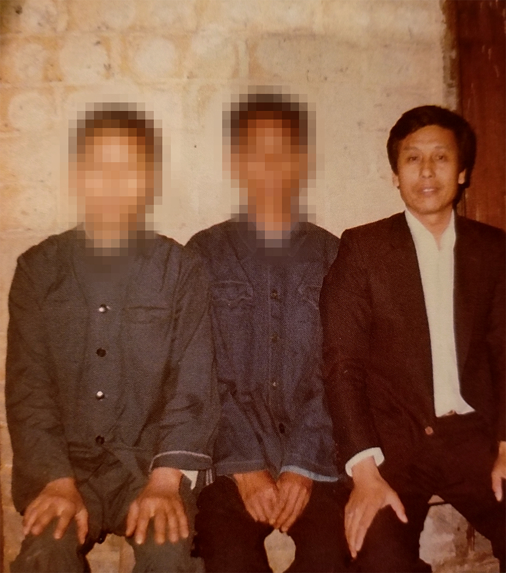 Three Chinese men sitting together. Two wear work uniforms, while the third wears a suit.
