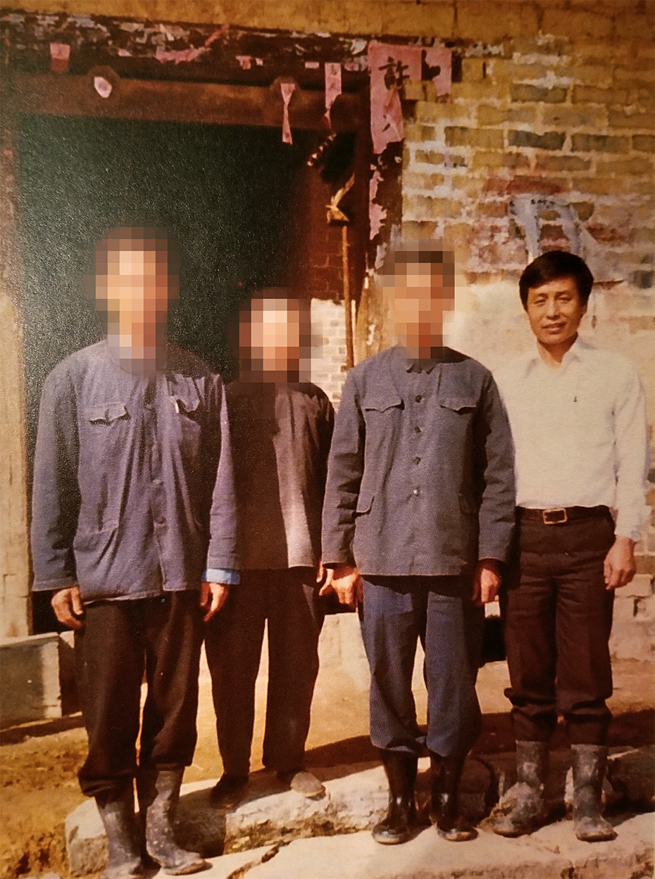Four reunited relatives stand together in their ancestral village in China