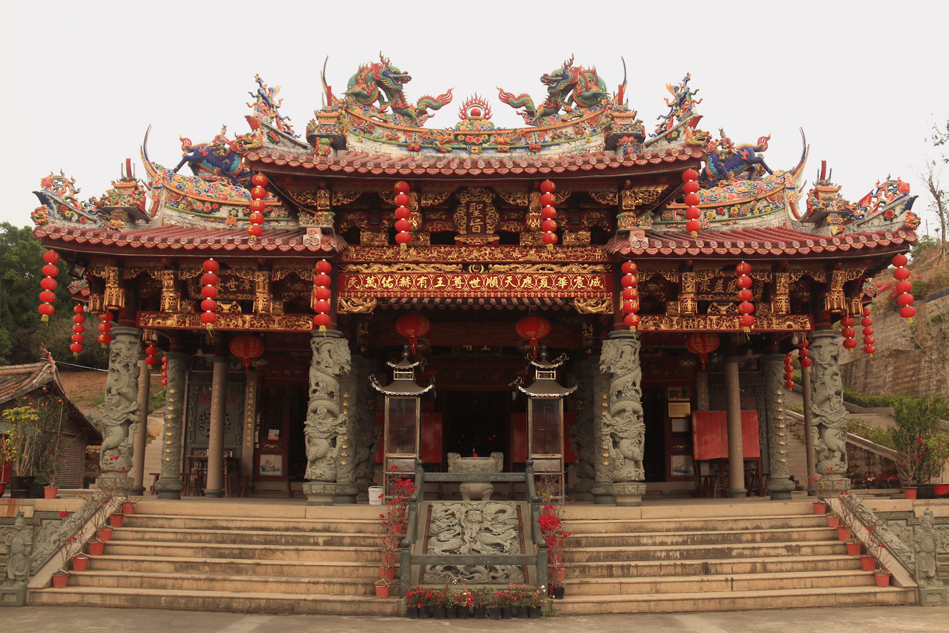 Ornate golden and red facade of the Hui Tek Chun Ong Temple in Puhou, China