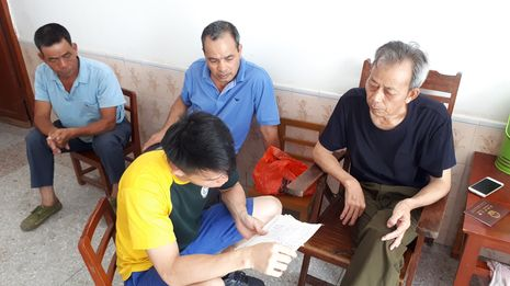 4 men looking at qiaopi 侨批 letters. Three older men are seated against the wall while 1 younger man is seated perpendicular to them, asking about the letters.
